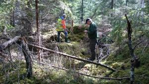 Ingången till jordkulan. Björn tar ut koordinaterna och Lars betraktar den stensatta bakväggen.